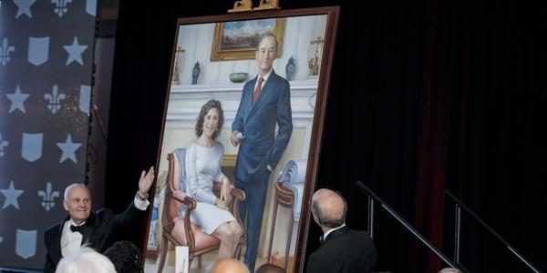 a man in tuxedo gestures to a large portrait of the Wrightons