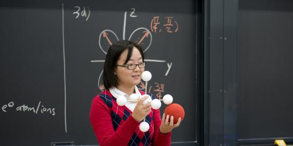 professor holding atom models