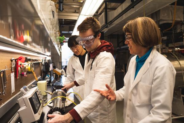 students and professor working in lab